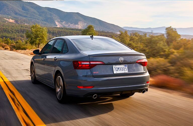 2020 Volkswagen Jetta GLI exterior rear shot with gray paint color driving on a country highway