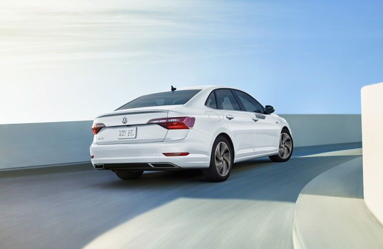 Rear passenger angle of a white 2020 Volkswagen Jetta driving around a corner