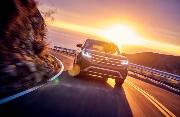 2021 Volkswagen Atlas exterior shot driving on a grassy mountain highway as the sun sets in the sky