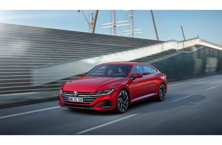 2021 Volkswagen Arteon exterior shot with red paint color driving by bleacher on a racetrack