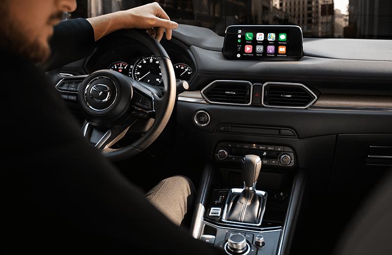 Man gripping steering wheel inside 2019 Mazda CX-5