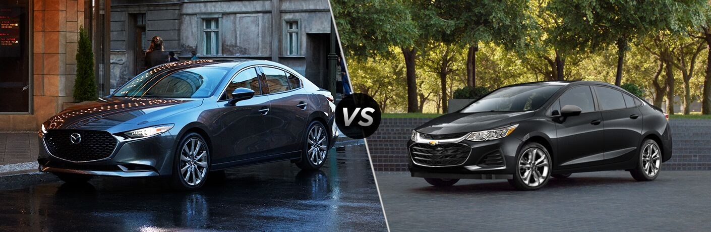 Gray 2019 Mazda3 Sedan on a City Street vs Black 2019 Chevy Cruze Sedan in a Park