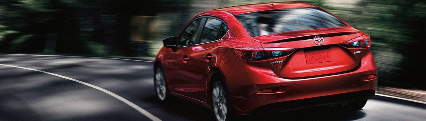 A rear left quarter photo of the 2018 Mazda3 sedan.