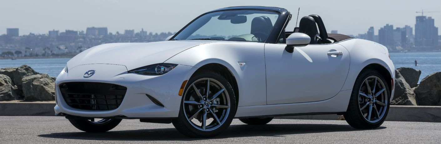 A front-left quarter photo of the 2019 Mazda MX-5 Miata with its soft top open.