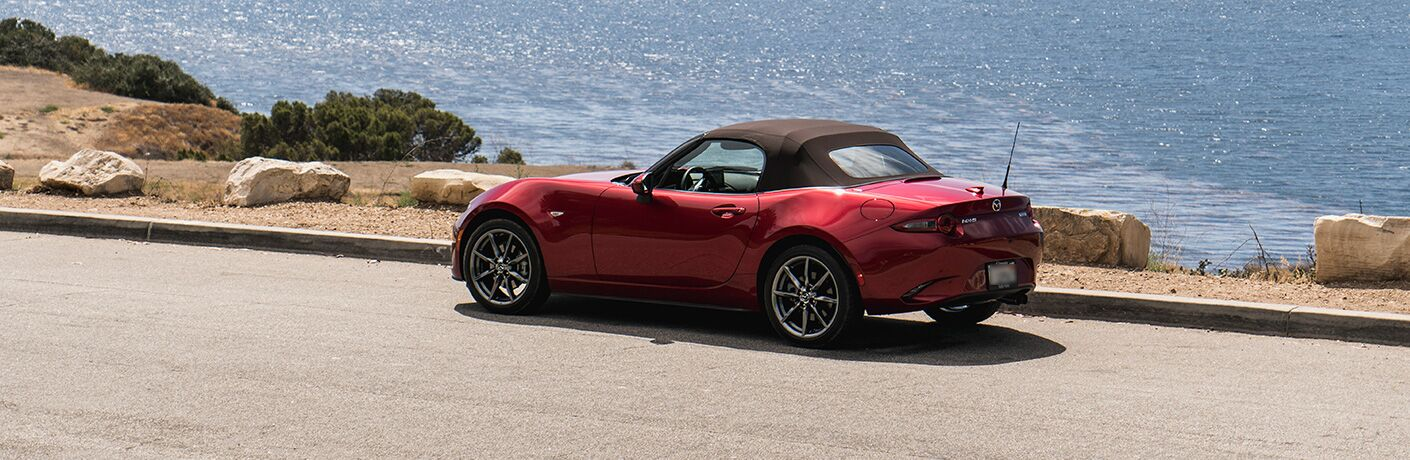 A left profile photo of the 2019 Mazda MX-5 Miata parked next to the ocean.