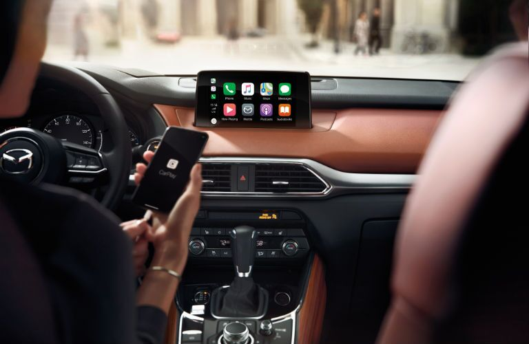 A photo of someone connecting a smartphone into the 2019 Mazda CX-3 Touring.