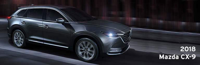 2018 Mazda CX-9 Written in White with Side and Front End View of Vehicle in Gray