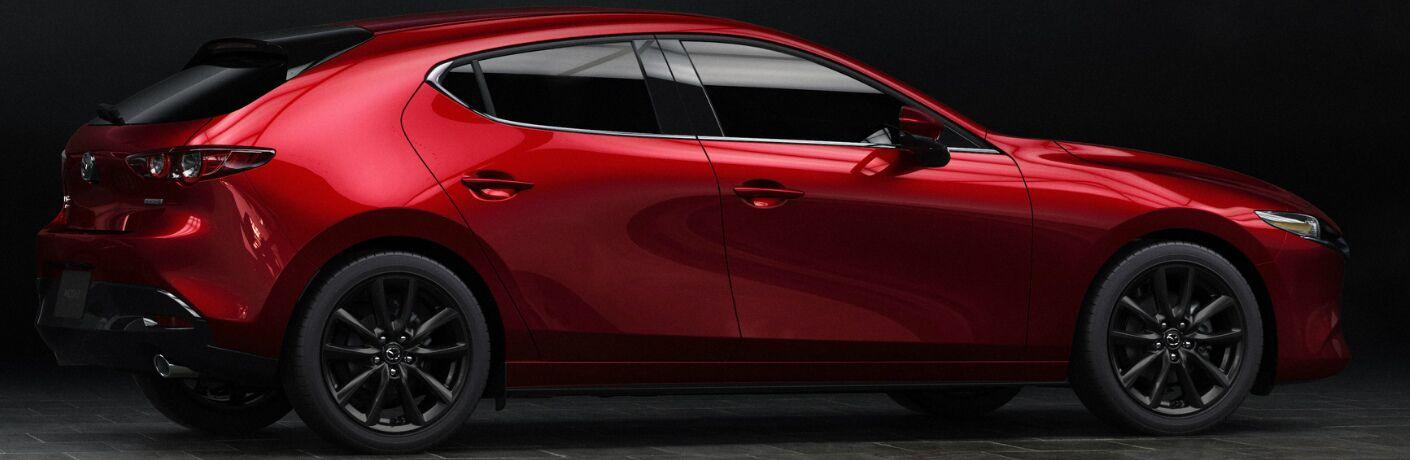 Passenger side exterior view of a red 2019 Mazda3 Hatchback
