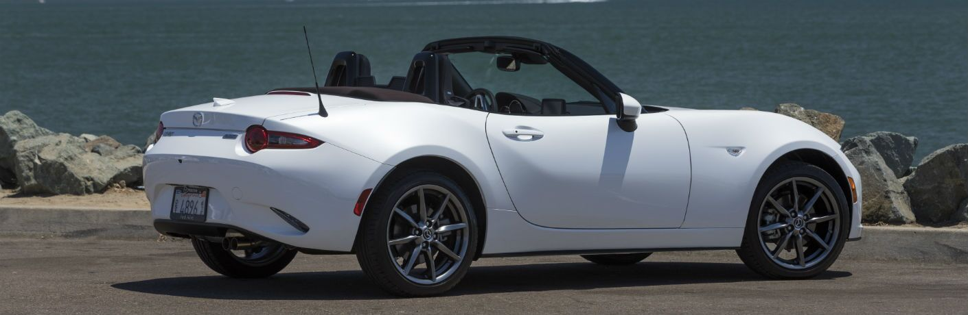 right side view of white mazda mx-5 miata with roof down