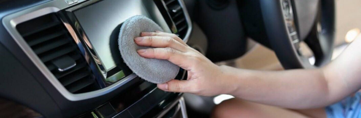 A woman cleaning a car's infotainment system