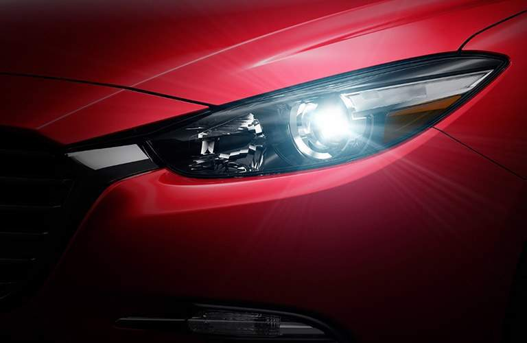 Closeup of headlight on red 2018 Mazda3