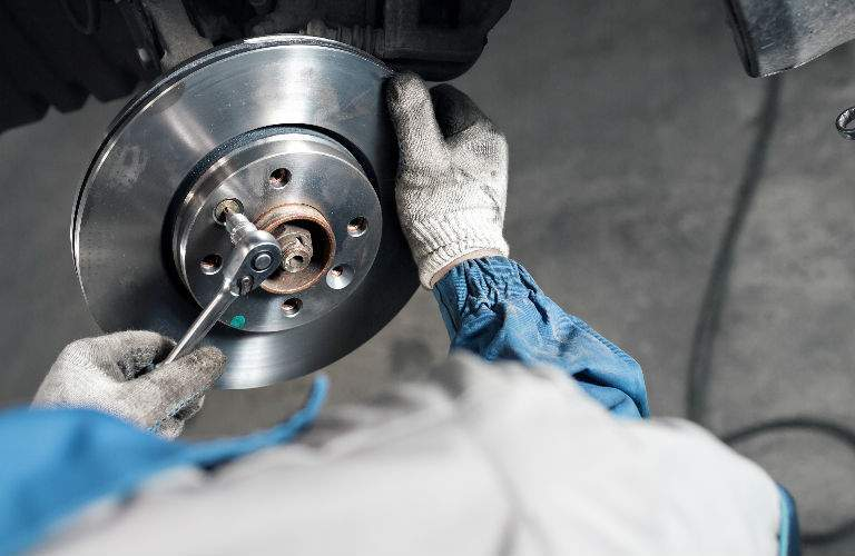 Mechanic Working on Part of Brake and Tire