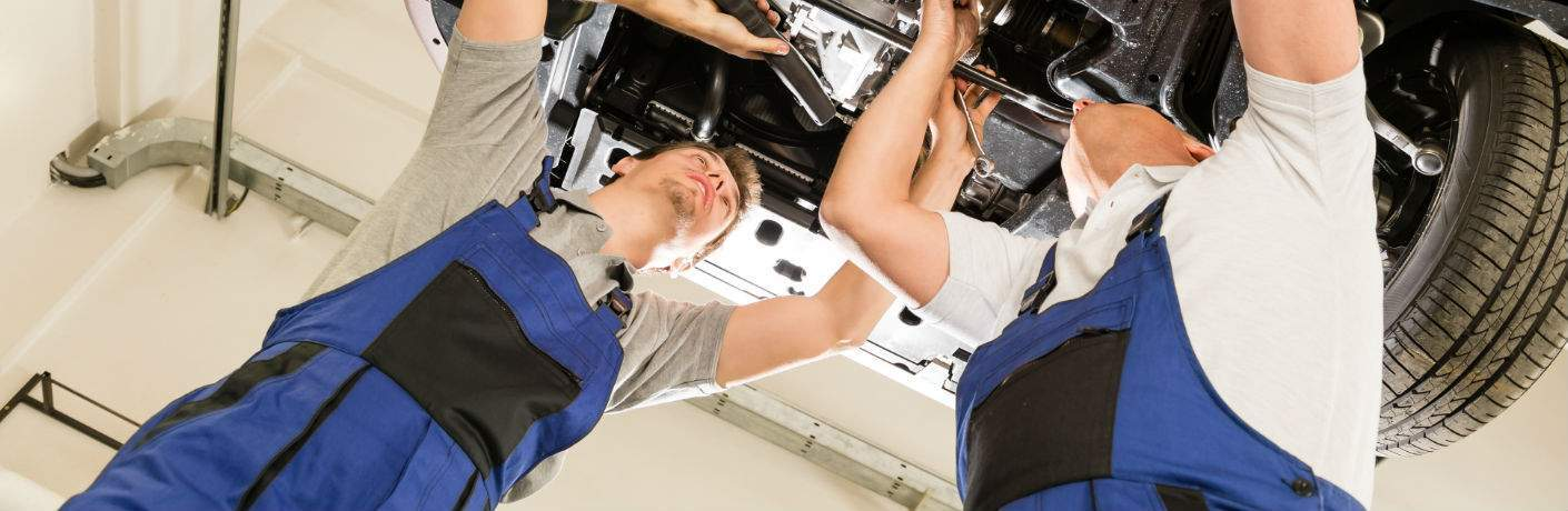 Two Mechanics Underneath Car in Service Center