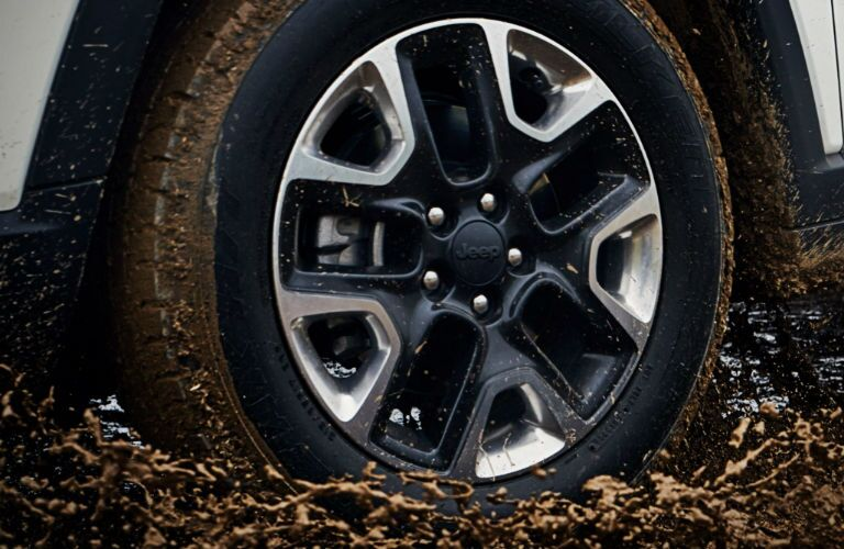 Jeep Model Close Up of Tire Traveling Through Mud With Black Spokes