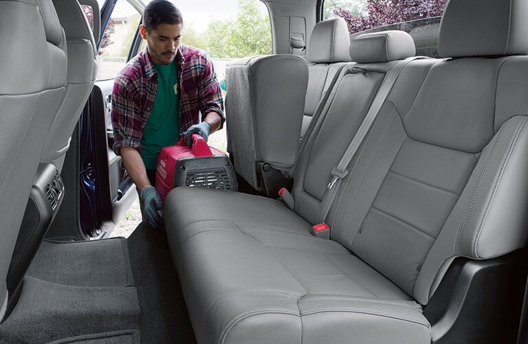 Man Holding a Machine in the Rear Seating Area of 2018 Toyota Tundra