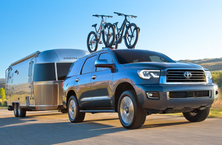 Dark Blue 2018 Toyota Sequoia Towing a Camping Trailer