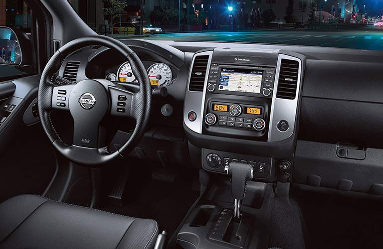 2018 Nissan Frontier interior front seating view of steering wheel, transmission, and dashboard screens
