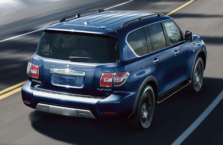 View of blue 2018 Nissan Armada driving down a paved street during the day