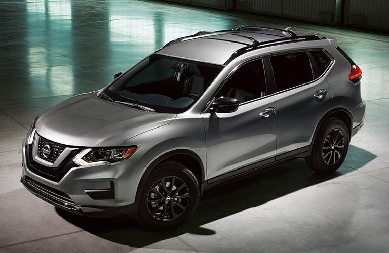 Side quarter profile of the 2018 Nissan Rogue parked in a grey warehouse