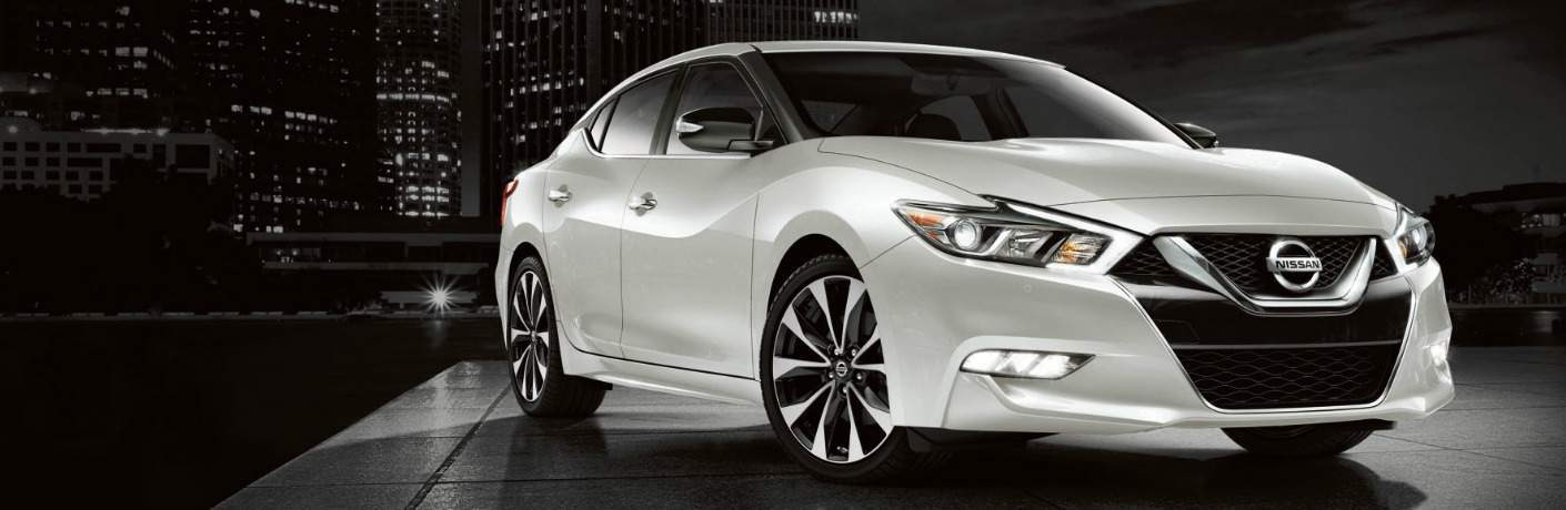 white 2018 Nissan Maxima against a city skyline background at night exterior front view