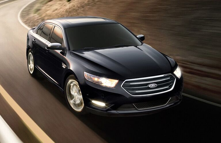 2018 Ford Taurus in black driving on a road