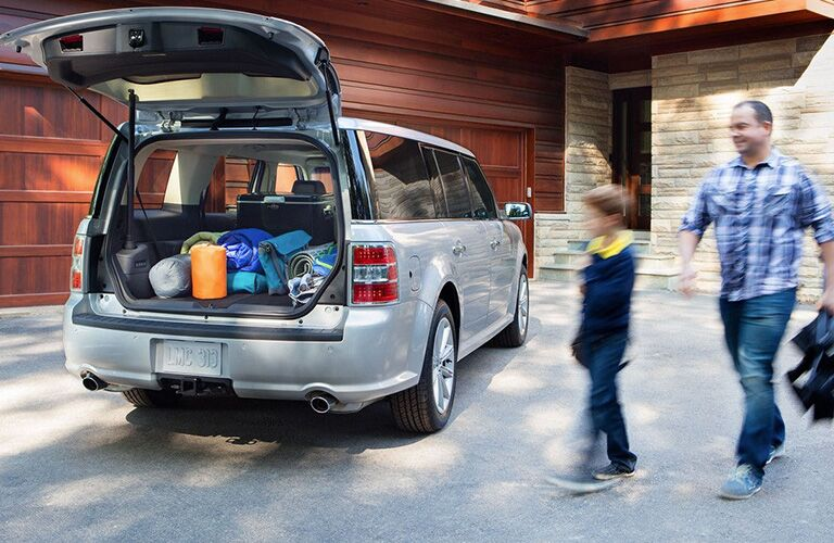 2018 Ford Flex exterior back fascia and passenger side open trunk with man and child walking towards it