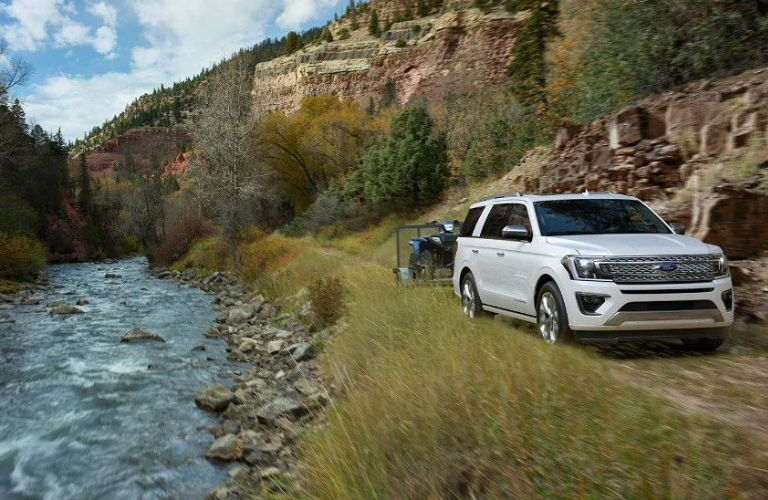 2018 Ford Expedition pulling a trailer next to a river