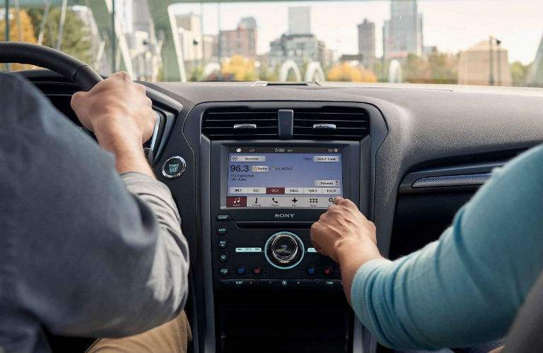 person using the display screen in a 2018 Ford Fusion