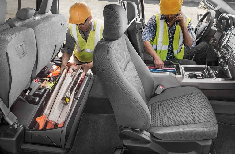 2018 Ford Super Duty with two construction workers accessing interior storage
