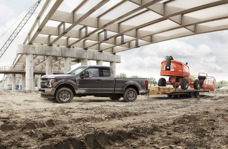 2018 Ford Super Duty pulling a cherry picker in construction site