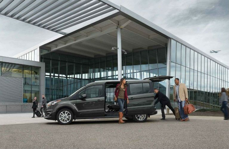 2018 Ford Transit Connect with people unloading luggage at an airport