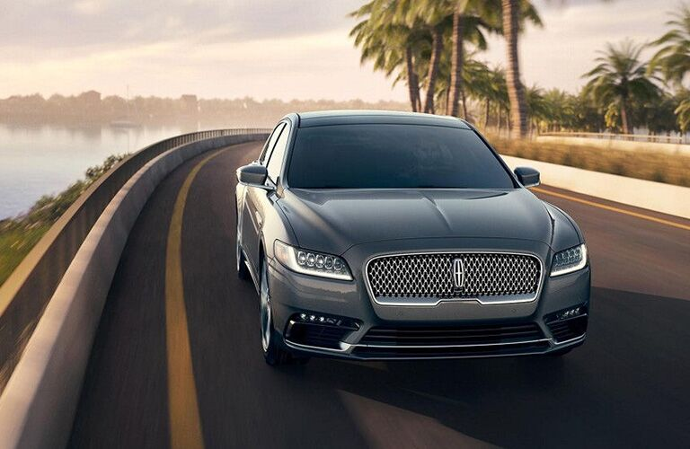 2018 Lincoln Continental driving on coastal road with palm trees behind it exterior front view