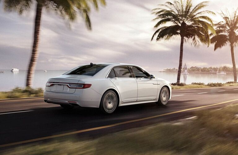 2018 Lincoln Continental exterior rear side view as it drives down coastal road with palm trees