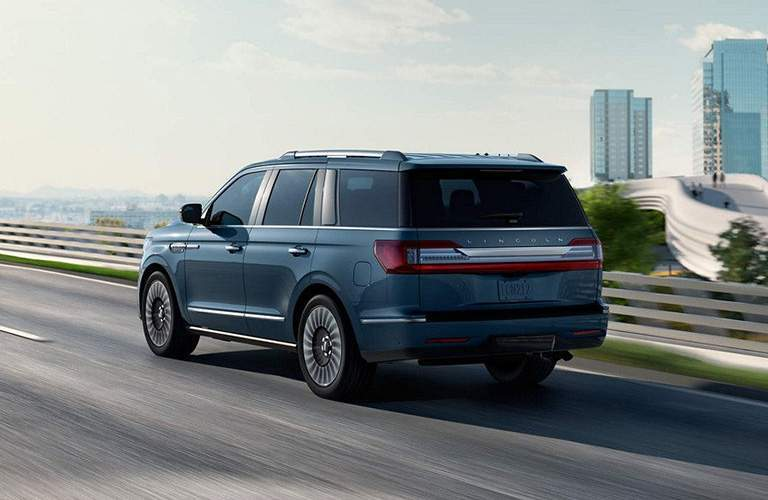 exterior rear quarter view of 2018 Lincoln Navigator driving on expressway exiting city