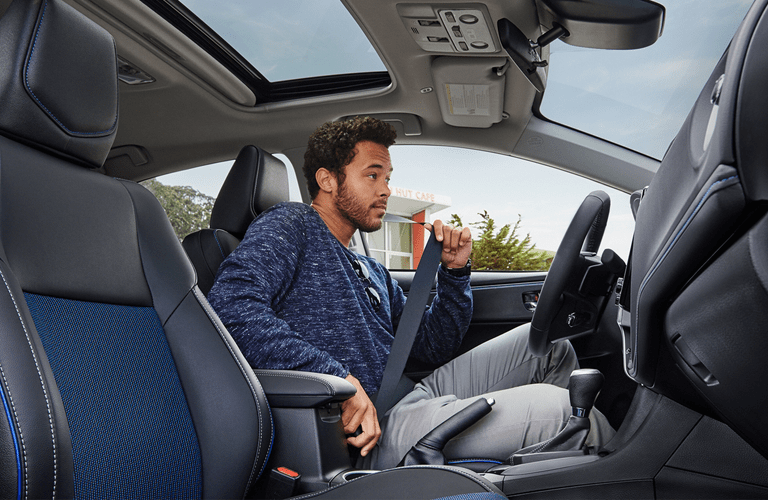 2018 Toyota Corolla interior front cabin with man buckling in