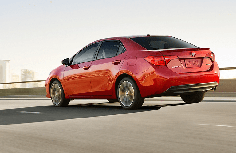 Rear shot of red 2018 Toyota Corolla driving over bridge