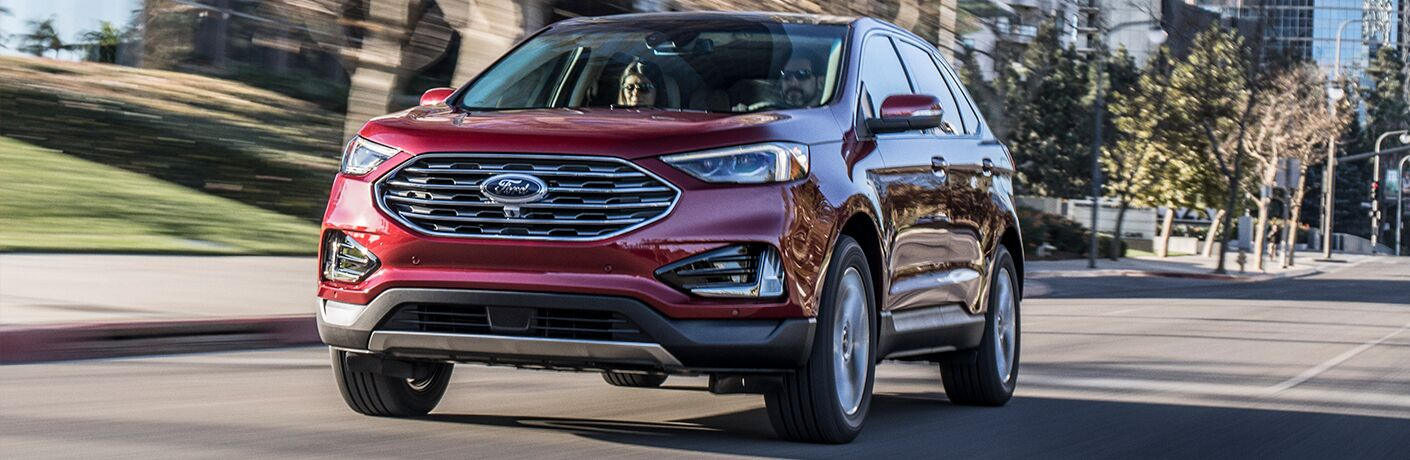Two people inside red 2019 Ford Edge driving on city street