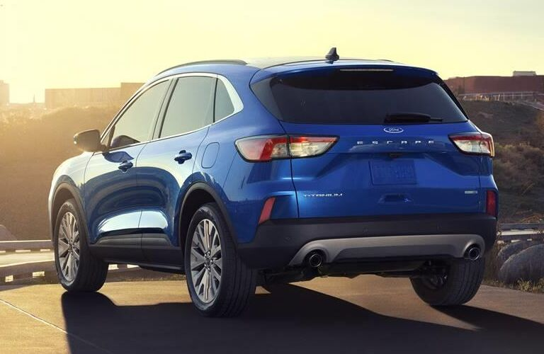2020 Ford Escape Titanium rear shot with blue paint color under a bright sunset