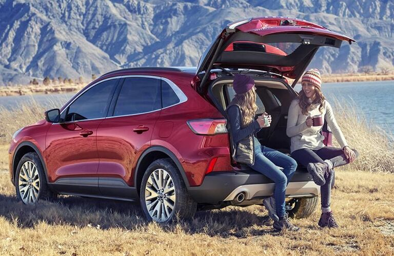2020 Ford Escape exterior shot with red paint color parked by a lake with its trunk open as two women drink coffee on its rear bumper