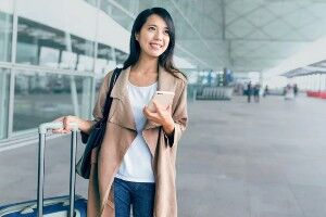 Individual holding phone and luggage