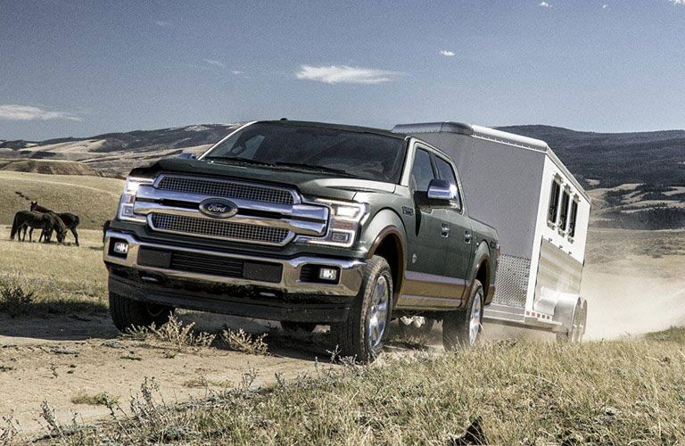 2018 Ford F-150 green towing a trailer