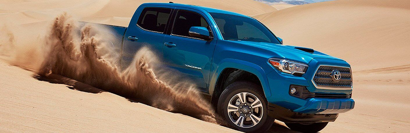Blue Toyota Tacoma Model Driving Through Sand Side and Front End View