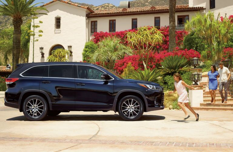 Side View of the 2017 Toyota Highlander in Navy with Kid Running Next to it