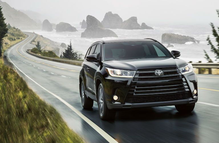 2017 Toyota Highlander Driving by body of Water Exterior View in Black