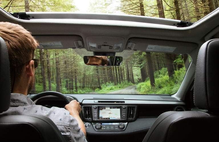 Driver in a 2018 Toyota RAV4 on a wooded road with the sunroof open