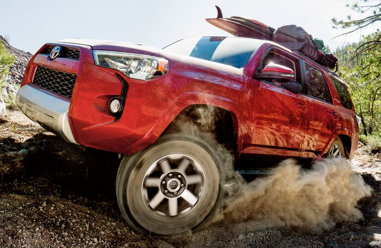 2019 Toyota 4Runner in red kicking up dirt on a trail