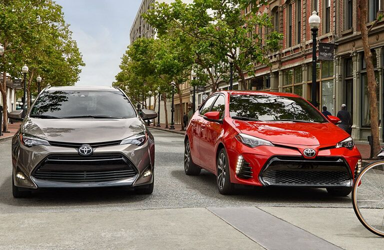 Two 2019 Toyota Corolla models stopped on the road waiting for pedestrians