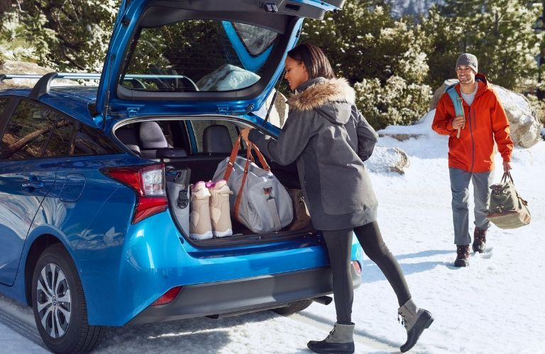 woman and man loading cargo into rear of 2019 Toyota Prius