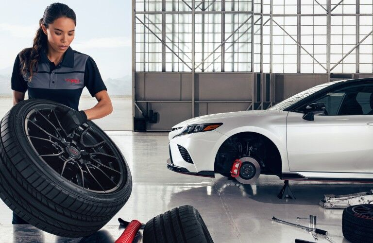 Woman holding wheel by white 2020 Toyota Camry TRD