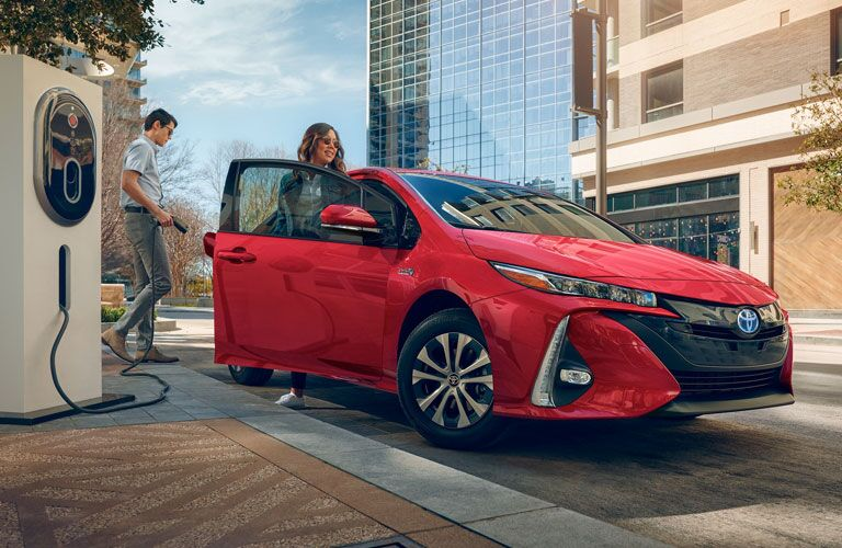 Two individuals charging red 2020 Toyota Prius Prime
